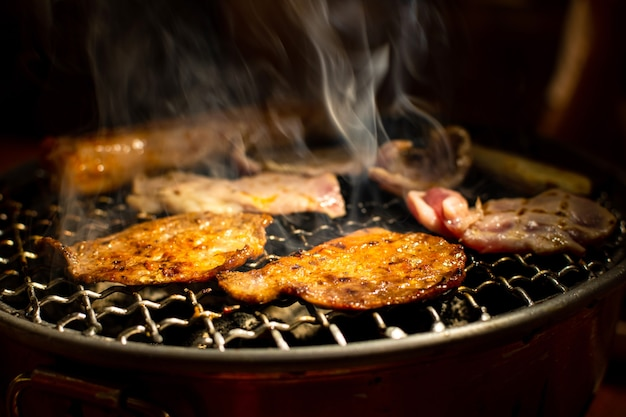Carne de porco ou vaca grelhada na grelha a carvão. cozinhando yakiniku estilo japonês