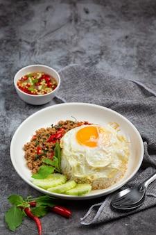 Carne de porco picada com manjericão com arroz e ovo frito
