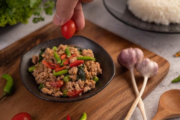 Carne de porco picada e arroz picados em uma placa preta.