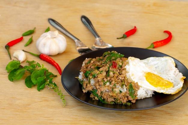 Carne de porco salgada com pimenta & manjericão folhas em chapa preta na mesa de madeira