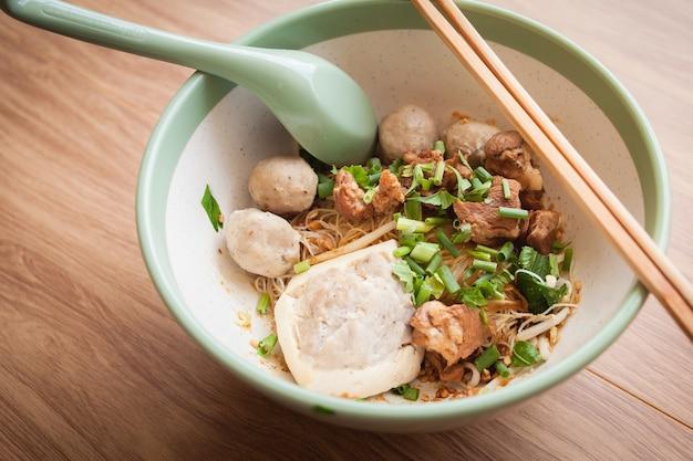 Carne de porco seca noolde almôndega e tofu na tigela e colher