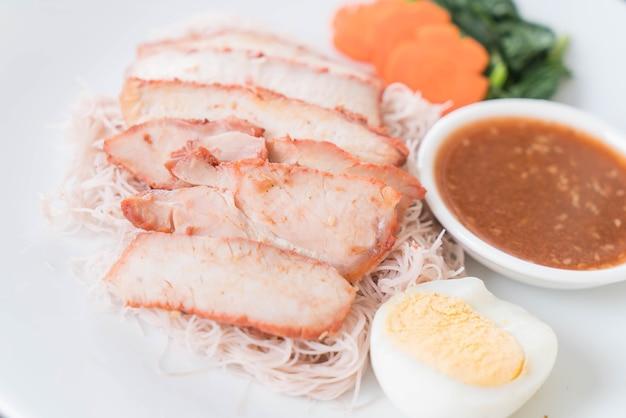 Carne de porco vermelha assada no molho com macarrão de trigo integral