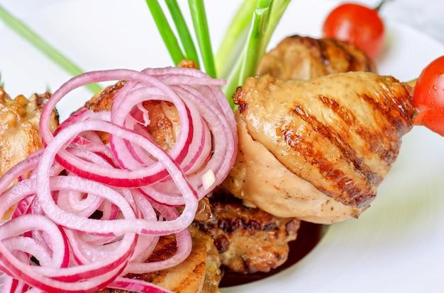 Carne de quibe grelhado com cebola e tomate em um prato branco