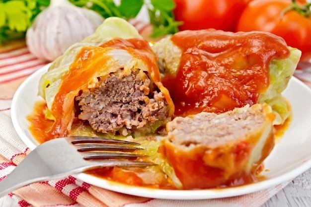 Carne de repolho recheado em folhas de repolho com molho de tomate e um garfo em um prato em um guardanapo, tomate, salsa e alho em um fundo de prancha de madeira clara
