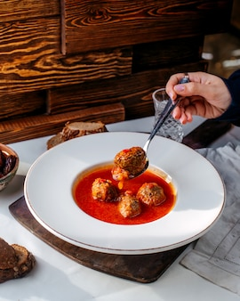 Carne de sopa de tomate vista frontal dentro de chapa branca sobre o backgorund branco