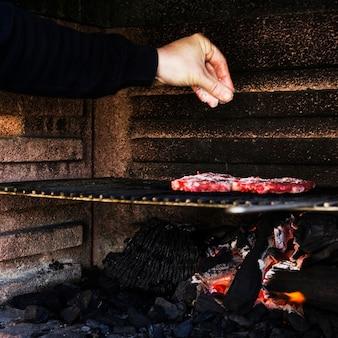 Carne de tempero de mão humana na churrasqueira