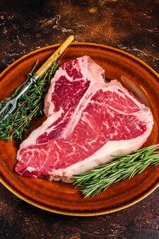 Carne de vaca crua porterhouse bife com ervas em um prato. fundo escuro. vista do topo.