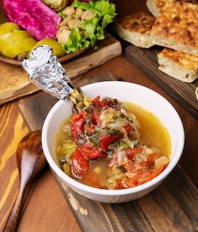 Carne de vaca, lâmpada, guisado de bolinho com tomate, pimentão e legumes em caldo