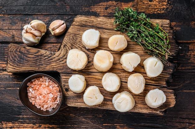 Carne de vieiras cozidas no vapor em uma placa de madeira.
