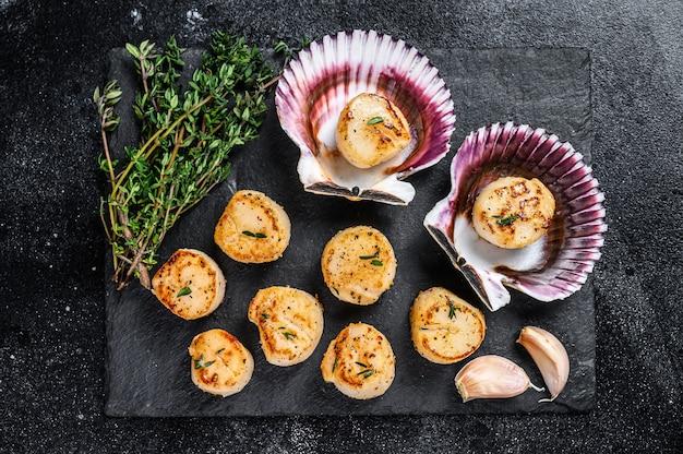 Carne de vieiras de frutos do mar fritos com manteiga em uma concha na mesa de madeira. vista do topo.