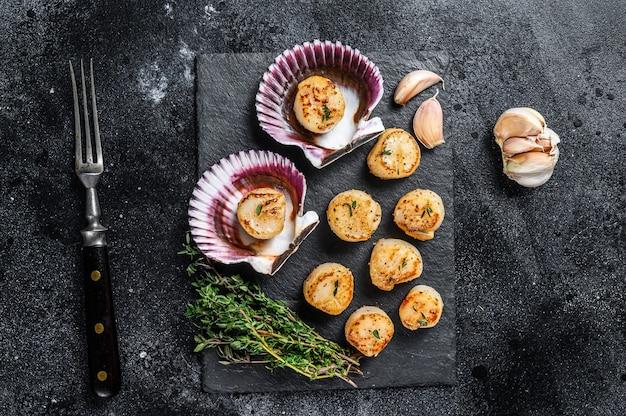 Carne de vieiras de frutos do mar fritos com manteiga em uma concha.