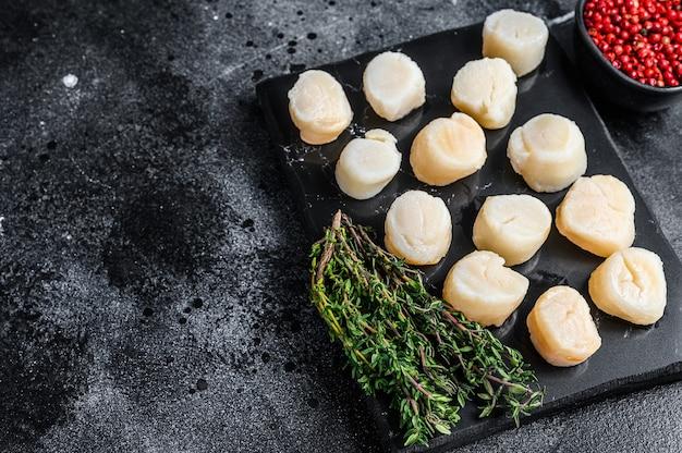 Carne de vieiras frescas de frutos do mar em uma placa de mármore. fundo preto. vista do topo. copie o espaço.