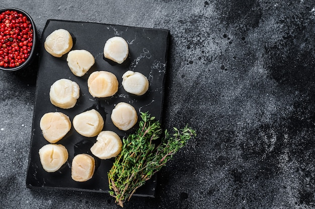 Carne de vieiras frescas de frutos do mar em uma placa de mármore.