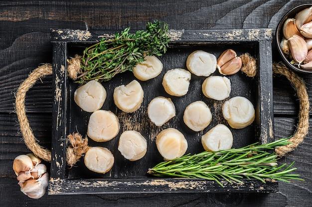 Carne de vieiras frescas em uma bandeja de madeira. fundo de madeira preto. vista do topo. Foto Premium