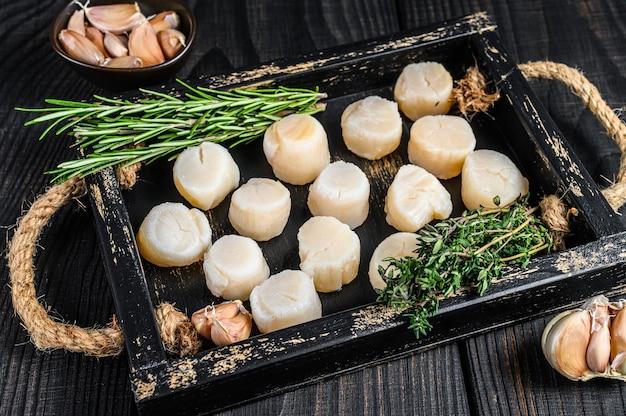 Carne de vieiras frescas em uma bandeja de madeira.