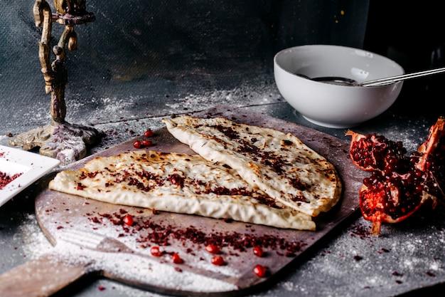 Carne deliciosa qutabs cheia de sumax na superfície de madeira marrom e cinza