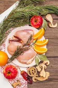 Carne desossada de frango cru com ervas e frutas no prato. cozinhar no dia de ação de graças