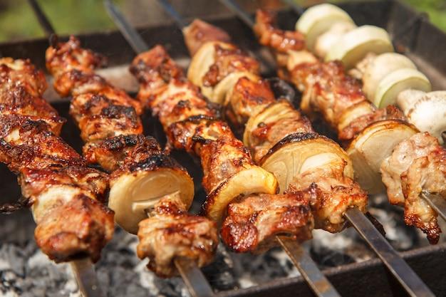 Carne e cebola no espeto, abobrinha e cogumelos no espeto são grelhados no carvão. cozinhar um prato de shish kebab no churrasco. piquenique, comida de rua. foco seletivo