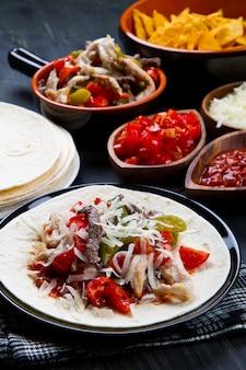 Carne e frango fajitas com pimentões coloridos em tortill