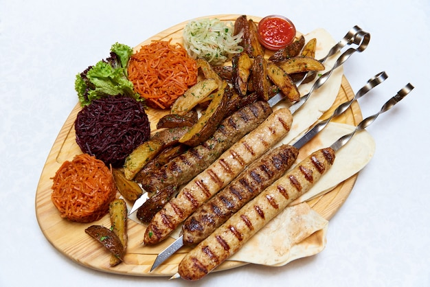 Carne e legumes em uma placa de madeira.