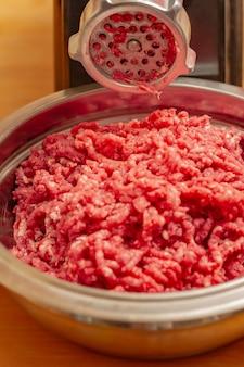 Carne e moedor. carne picada e moedor de carne. máquina de moer carne picando carne moída crua.