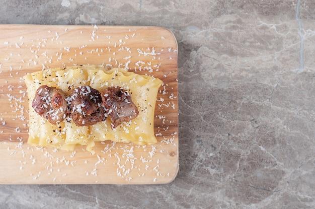 Carne em folhas de lasanha no tabuleiro, no mármore.