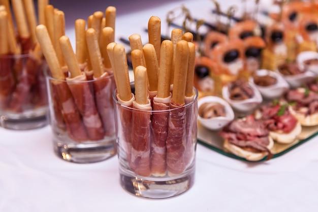 Carne embrulhada em palitos de pão palitos de pão com presunto em um copo buffet de comida deliciosa