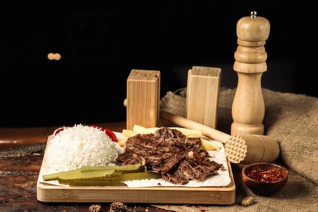 Carne fatiada com arroz cozido e fatias de picles
