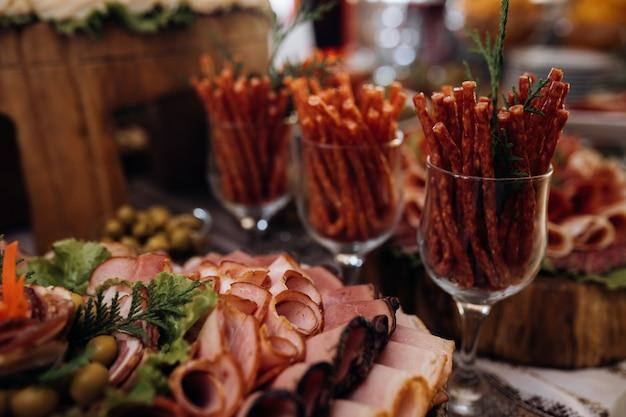 Carne fatiada e outros petiscos estão sobre a mesa