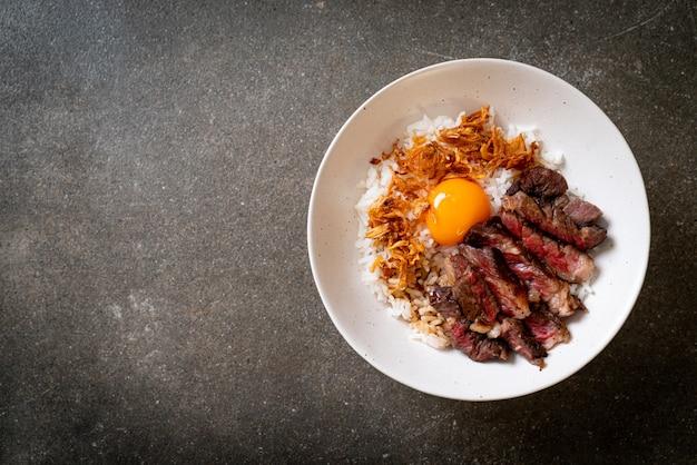 Carne fatiada na tigela de arroz coberto com ovo