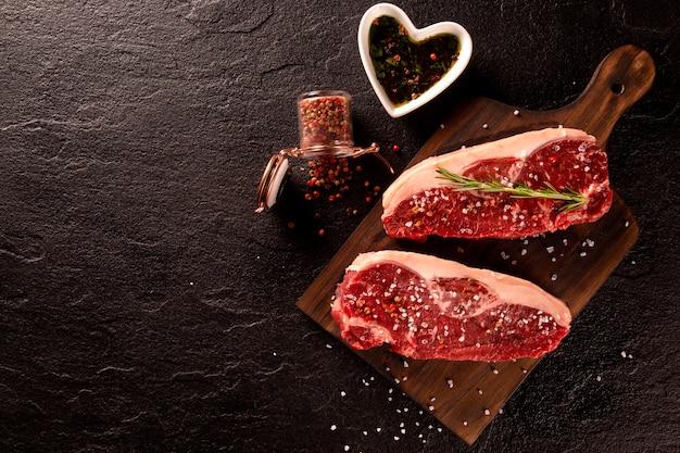 Carne fresca com ingredientes para cozinhar em fundo escuro, vista superior.