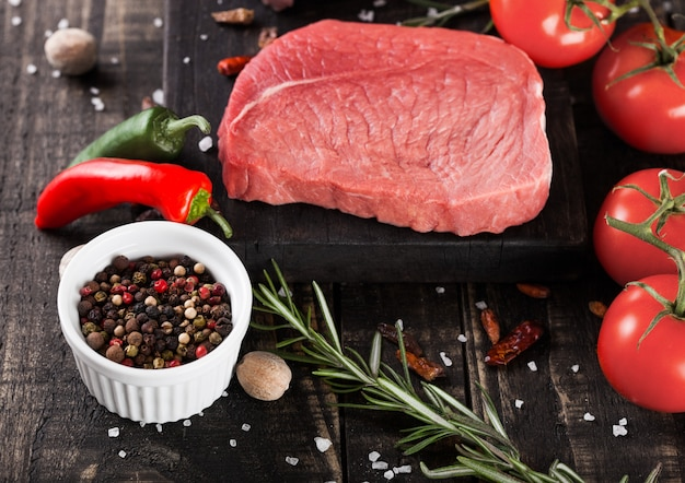 Carne fresca de bife cru na tábua da cozinha de madeira com tomate e pimenta