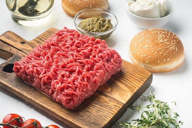 Carne fresca de bovino picada para hambúrgueres de almôndega com pãezinhos de gergelim, numa tábua de madeira, numa mesa de pedra branca