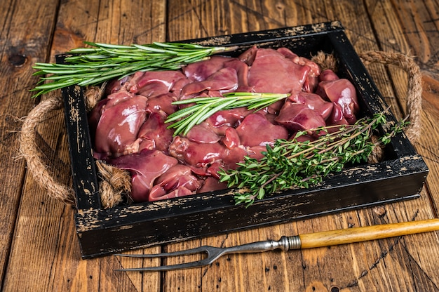 Carne fresca de miudezas de fígado de frango cru em uma bandeja de madeira. mesa de madeira. vista do topo.