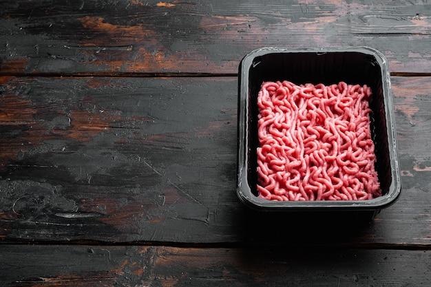 Carne fresca picada em conjunto de bandeja de embalagem de caixa de plástico, na velha mesa de madeira escura