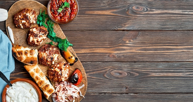 Carne frita. bolinhos de carne ou costeletas - kofte turco feito de cordeiro e boi com queijo e especiarias. em uma travessa de madeira com legumes grelhados, ervas e molho. layout com espaço de cópia