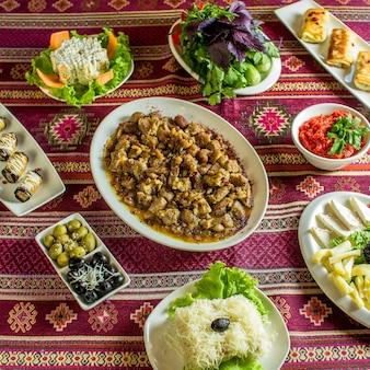 Carne frita com castanhas, servida com vários alimentos no tapete colorido