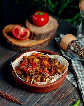 Carne frita com cogumelos e legumes na mesa