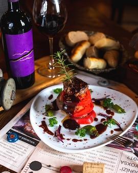 Carne frita com fatias de tomate, verduras, molho, raminho de alecrim servido com vinho