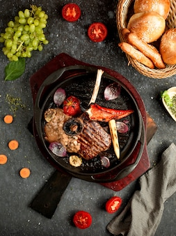 Carne frita com legumes e cogumelos em uma frigideira de alumínio