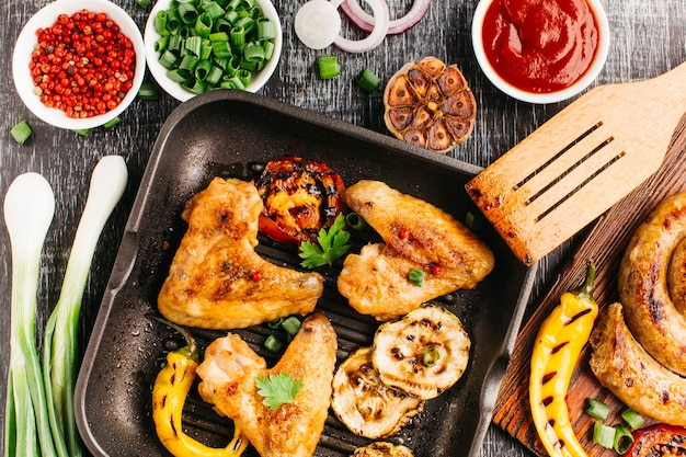 Carne frita com legumes e salsicha espiral na mesa de madeira