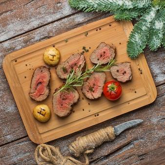 Carne frita com legumes na placa de madeira