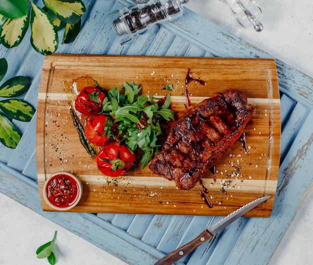 Carne frita com legumes na vista superior da placa de madeira