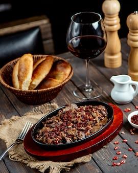 Carne frita com romã e copo de vinho tinto