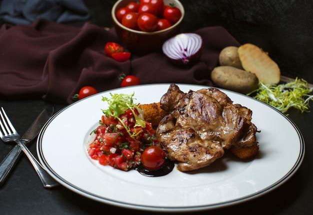 Carne frita com salada de tomate picado