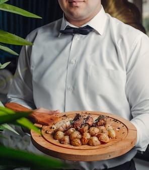 Carne frita e batata na placa de madeira