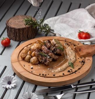 Carne frita e cogumelos na placa de madeira