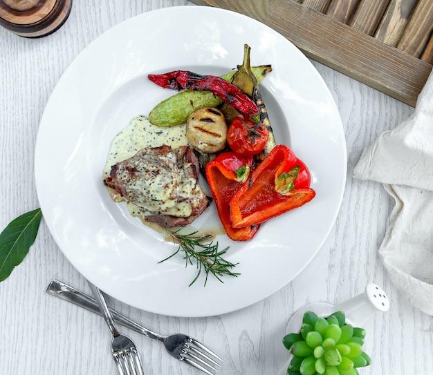 Carne frita em molho cremoso com legumes cozidos