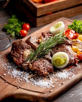 Carne frita servida com legumes grelhados, cebola e raminho de alecrim