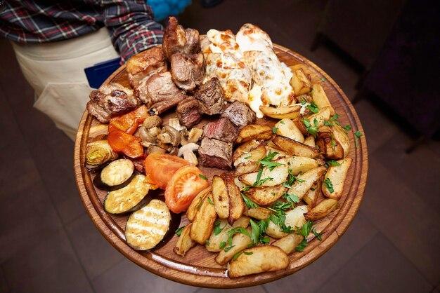 Carne fritada e legumes cozidos em uma placa de madeira nas mãos de um garçom em um restaurante.